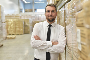 Portrait lächelnder Geschäftsmann/ Unternehmer im Warenlager einer Spedition // Portrait of a smiling businessman/ entrepreneur in the warehouse of a forwarding agency