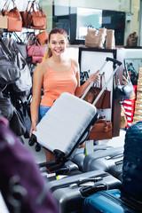 Teenager girl buying large wheeled plastic luggage bag