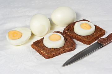 Eggs and two pieces of rye bread on the white napkin
