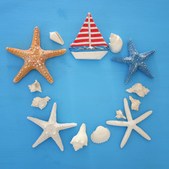 nautical and summer holidays concept with sea life style objects, seashells and starfish over blue wooden background.