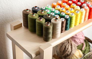 Set of color sewing threads on wooden shelf