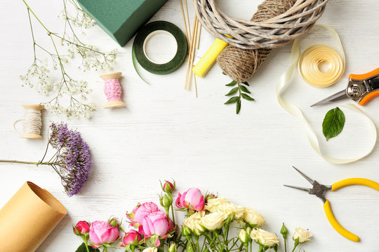 Florist equipment with flowers on wooden background, top view