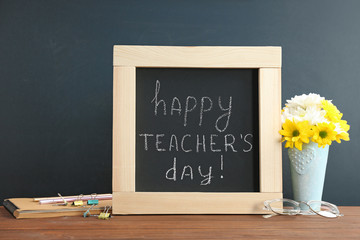 Little blackboard with inscription HAPPY TEACHER'S DAY, flowers and stationery on table