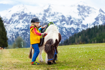 Kids riding pony. Child on horse in Alps mountains
