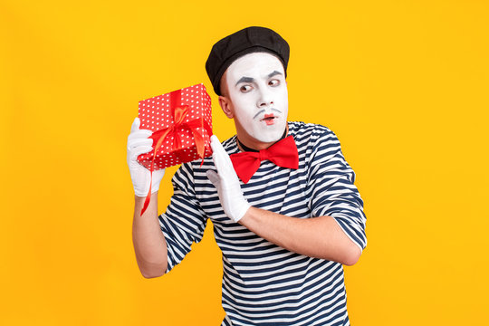What is inside box? Puzzled mime man holding red box