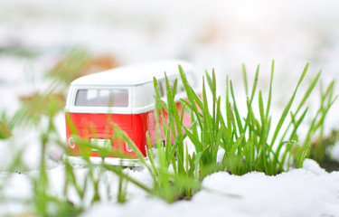 Lonely and funny bus trip. Adventure and holiday concept. Miniature toy bus in the middle of a tall grass.