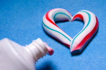 Healthy teeth. Hygiene of the oral cavity. Colored toothpaste from a tube. Pasta in the form of a heart