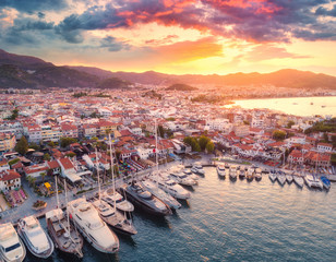 Aerial view of boats and yachts and beautiful architecture at sunset in Marmaris, Turkey. Landscape with boats, sea, colorful sky, houses, city, mountains. Top view of harbor with yacht and sailboat