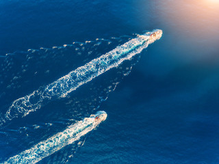 Yacht at the sea. Aerial view of luxury floating ship at sunset. Colorful landscape with boat in marina bay, blue sea. Top view from drone of yacht. Luxury cruise. Seascape with motorboat. Ocean