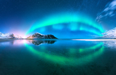 Aurora reflected in water. Northern lights in Lofoten islands, Norway. Blue sky with polar lights. Night landscape with aurora, sea with sky reflection, beach, mountains. Polar lights. Aurora borealis