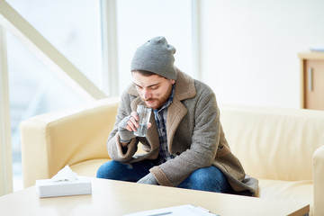 Young homeless man in shabby clothes sitting on sofa in social support center and drinking water