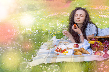 Happy girl resting on a picnic in the park. Lunch on green grass. Glade with flowers. Spring in the Netherlands