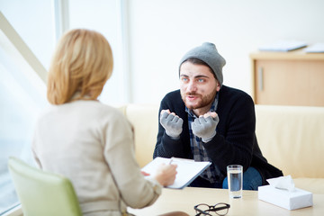 Young refugee in need explaining his problems to psychologist during session in social support center