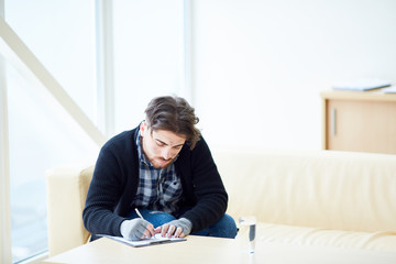Young refugee or terrorism victim sitting in center of social support and writing down information about his social situation