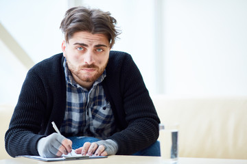Dirty homeless man looking at camera while filling in papers in the center of social support