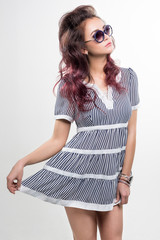 Studio portrait of a young attractive woman in striped short dress with stylish sunglasses posing at camera. White background.