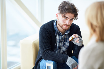 Young male refugee with bottle of pills listening to his psychologist recommendations