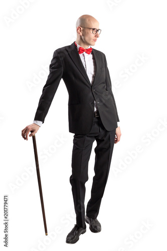 60b269ca5b Full length portrait of a slim tall man in a black suit with red bow tie  resting on a walking stick. Isolated on white.