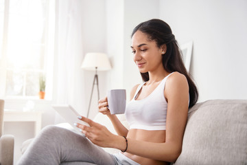 Cozy reading. Pleasant young woman sitting on the sofa and reading from tablet while drinking tea and smiling