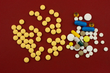 Color Capsules and tablets. Pharmaceutical medicine concept. Red background