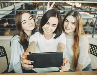 Three young happy women taking selfie at cafe
