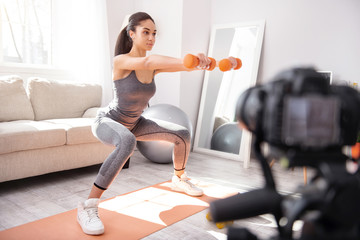 Exercises for perfect figure. Beautiful athletic woman holding dumbbells and doing squats in the living room while recording herself on camera