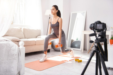 Exercising tutorial. Fit young woman doing lunges and holding dumbbells while recording herself on complex