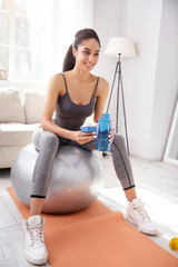 Proper hydration. Upbeat young woman sitting on the yoga ball holding a blue battle of water, staying hydrated during the workout session