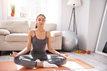 Freeing mind from worries. Charming fit woman sitting on the yoga mat in the Lotus pose and meditating while folding her fingers in chin mudra