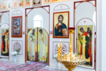 interior church with candles, candlesticks, icons and altar
