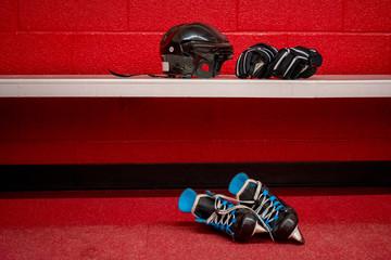 Hockey skates, helmet and gloves in locker room with copy space