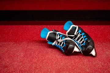 Kids hockey skates, lying in locker room floor with copy space