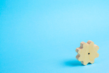 A wooden gear in the corner on a blue background. Minimalism, a place for text. Technology and business, an uncommon simple background.