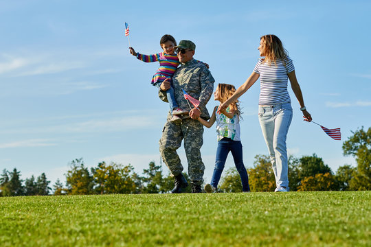 Soldier with his family are walking with usa flags. Father came back grou US army and wealking with his daughters and wife on the grass.