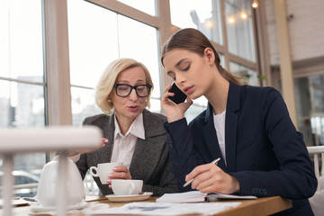 Leading business. Determined young businesswoman talking on the phone and taking notes