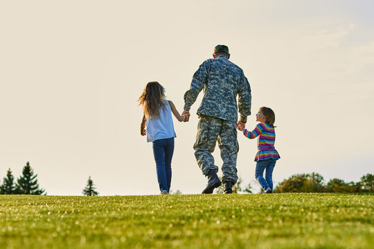 Soldier walking with little girls holding hands. Back view, father and daughters are walking together.