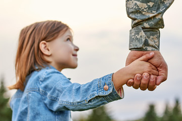 Soldier holding hand of little girl, close up. Hands of father and daughter.