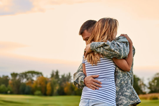 Soldier is hugging a woman outdoor. Reunion of a couple in the evening park.