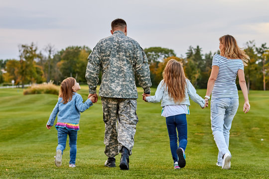Back view soldier's family walking. Soldier at vacation. Four family members walking together holding hands.