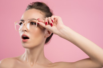 Surprise. Young woman in glasses is looking aside having ones eyes wide open in amazement. Isolated on pink background
