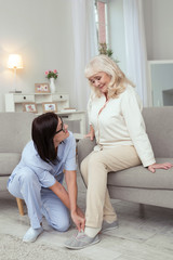 Chronic disease. Happy elder woman smiling while caregiver putting on slippers