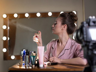 Profile of young elegant woman is sitting backstage and spraying perfume aside with closed eyes. She is recording video for her beauty blog using camera
