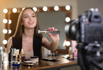 Luxury item. Cheerful girl is sitting at table and recording makeup video for her internet blog. She is demonstrating mascara to professional camera with joy. Selective focus