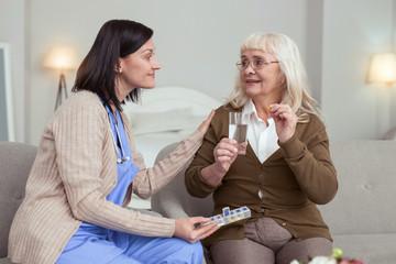 Medication treatment. Careful senior woman taking pills from nurse while wearing glasses
