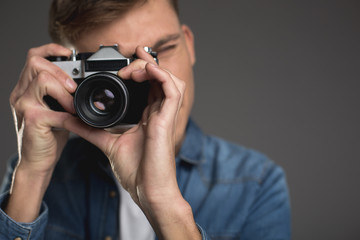 Hobby concept. Young man taking photo with old camera. Focus on hands holding device. Copy space in right side. Isolated on background