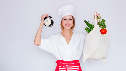 woman in cook uniform holding with different vegetables and black alarm clock