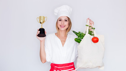 woman in cook uniform holding with different vegetables and prize cup