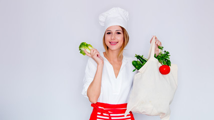 woman in cook uniform holding with different vegetables and showing salad leaves