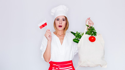 woman in cook uniform holding bag with different vegetables and polish flag