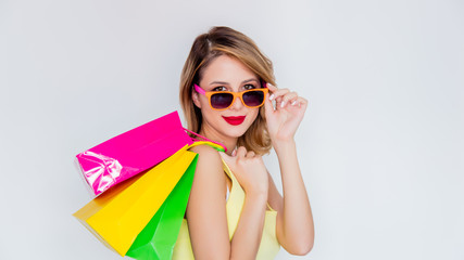 Young redhead girl in sunglasses with shopping bags on white background